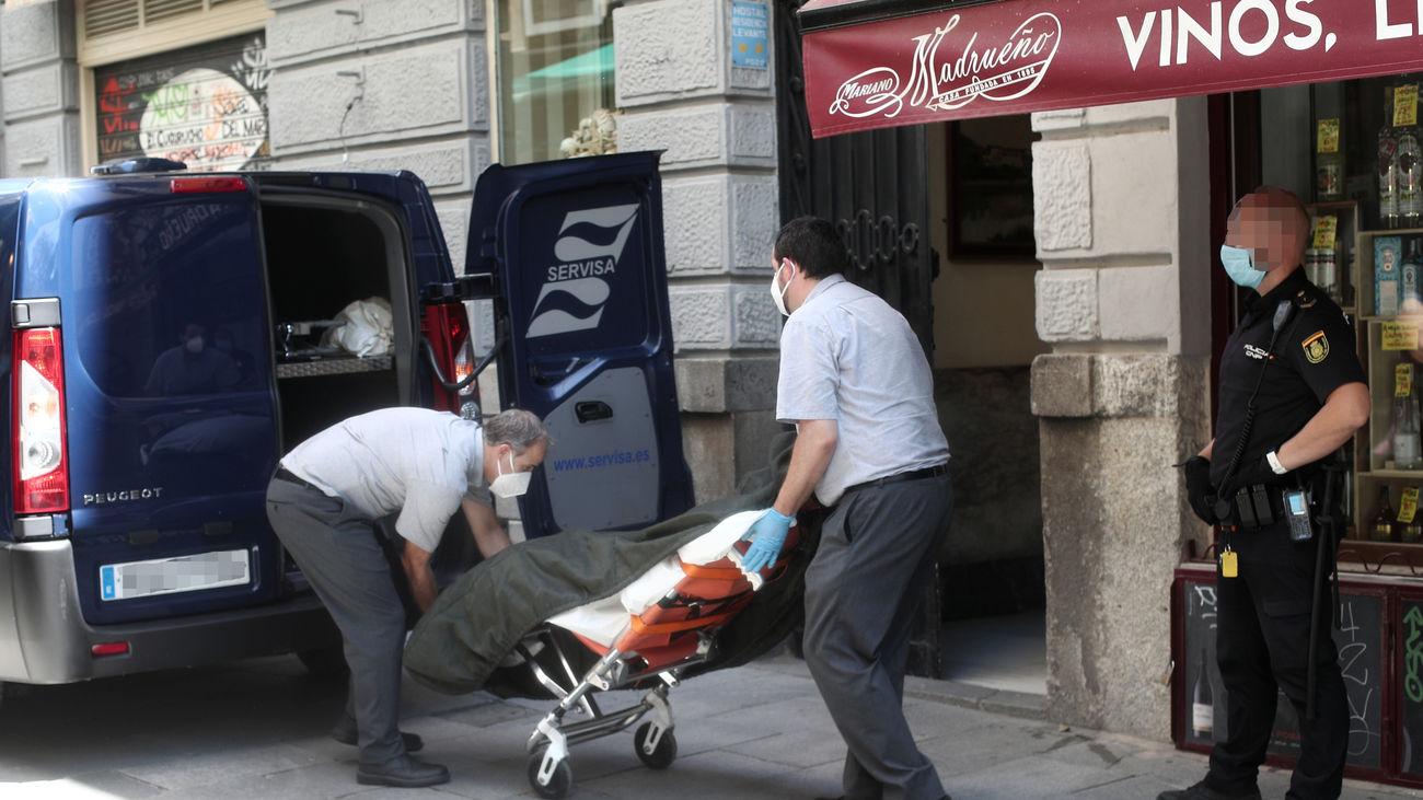 Dos trabajadores de una funeraria recogen los cuerpos sin vida de una mujer y su hijo hallados muertos en un hostal de Madrid