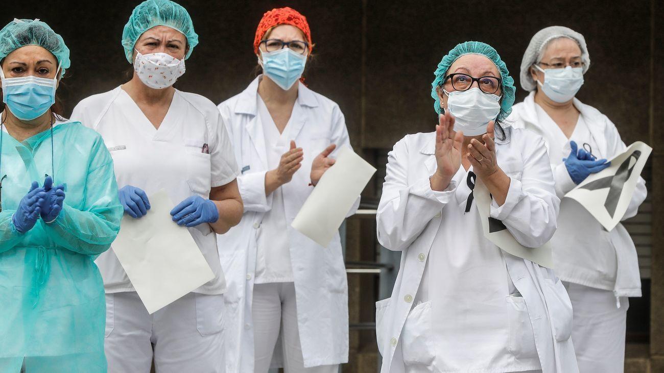 Un grupo de sanitarios aplaude a las puertas de un centro hospitalario