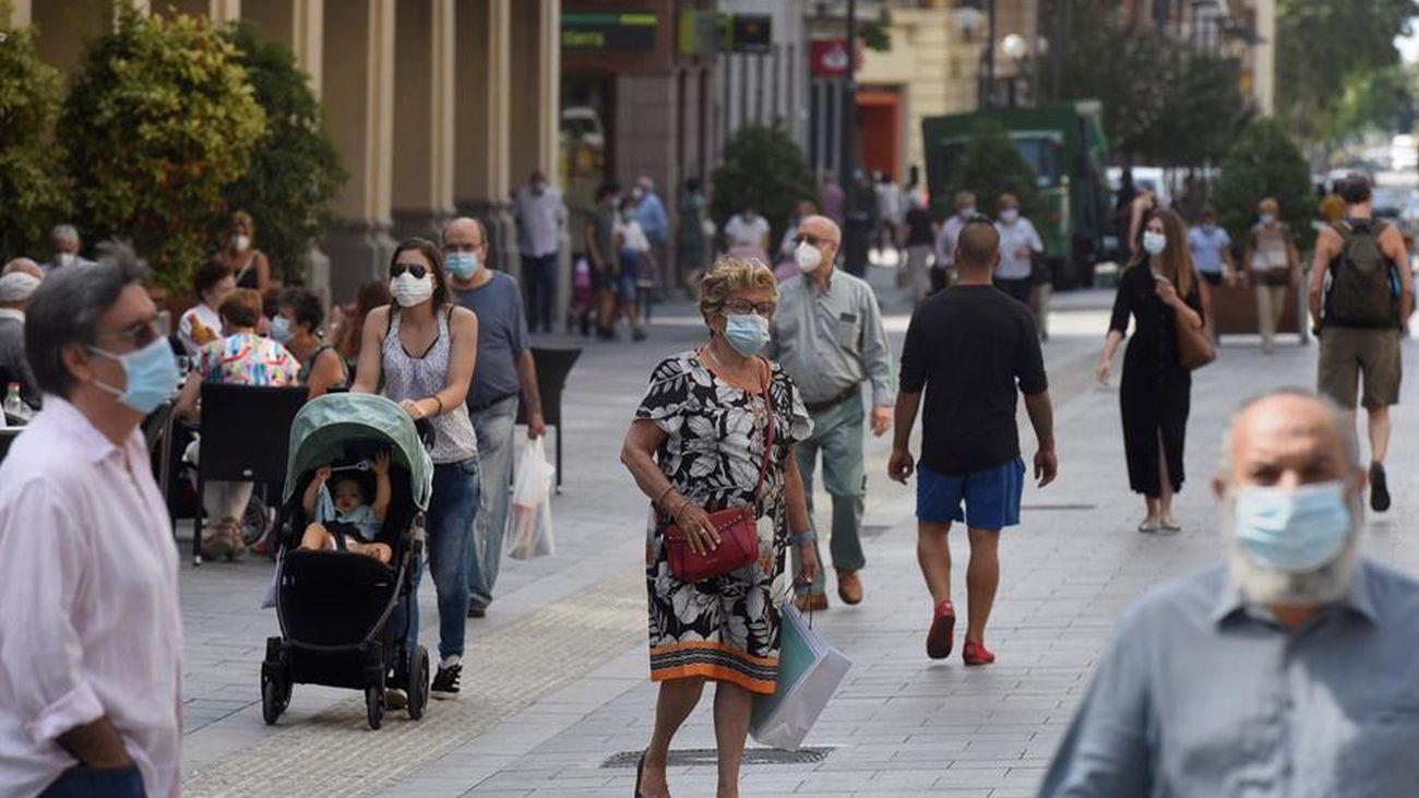 Varias personas en la calle con su mascarilla