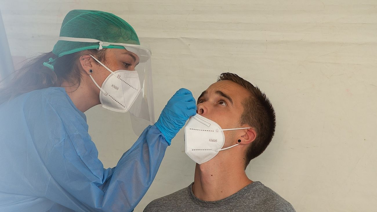Una enfermera realiza una prueba PCR a un joven