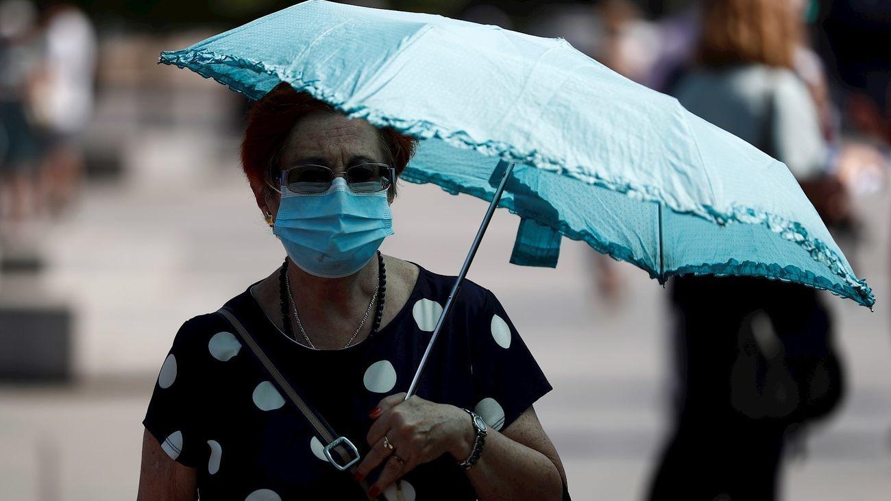 Una mujer pasea con mascarilla y paraguas para refugiarse del calor