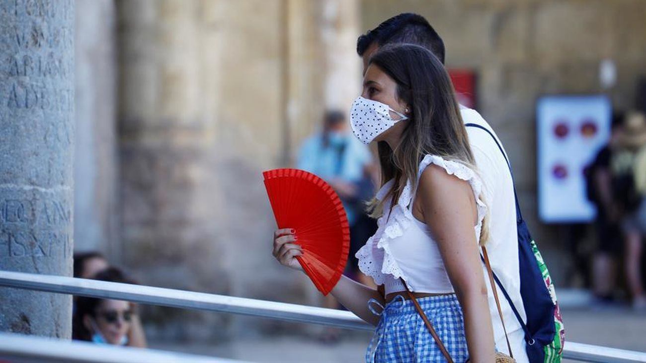 Una mujer pasea con la mascarilla puesta