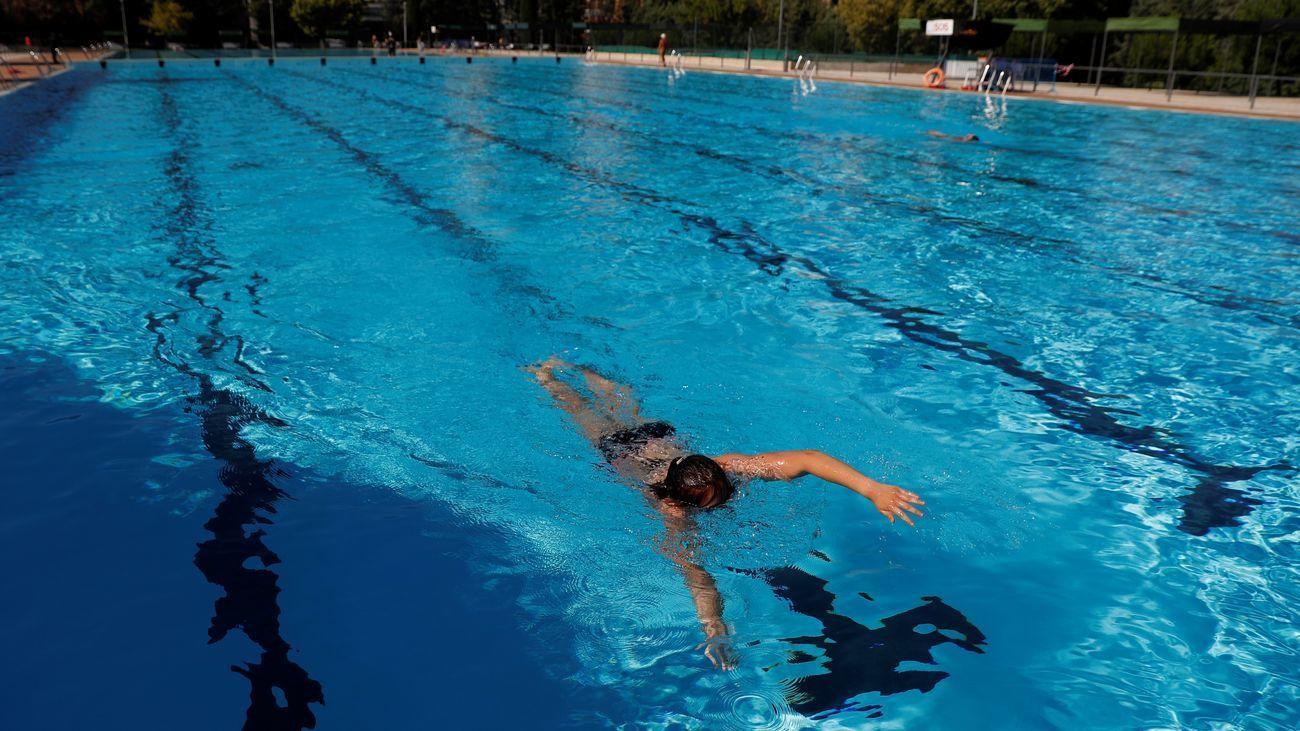 Una persona nada en una piscina municipal