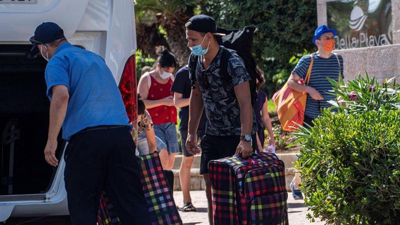 Varios turistas transportando sus maletas