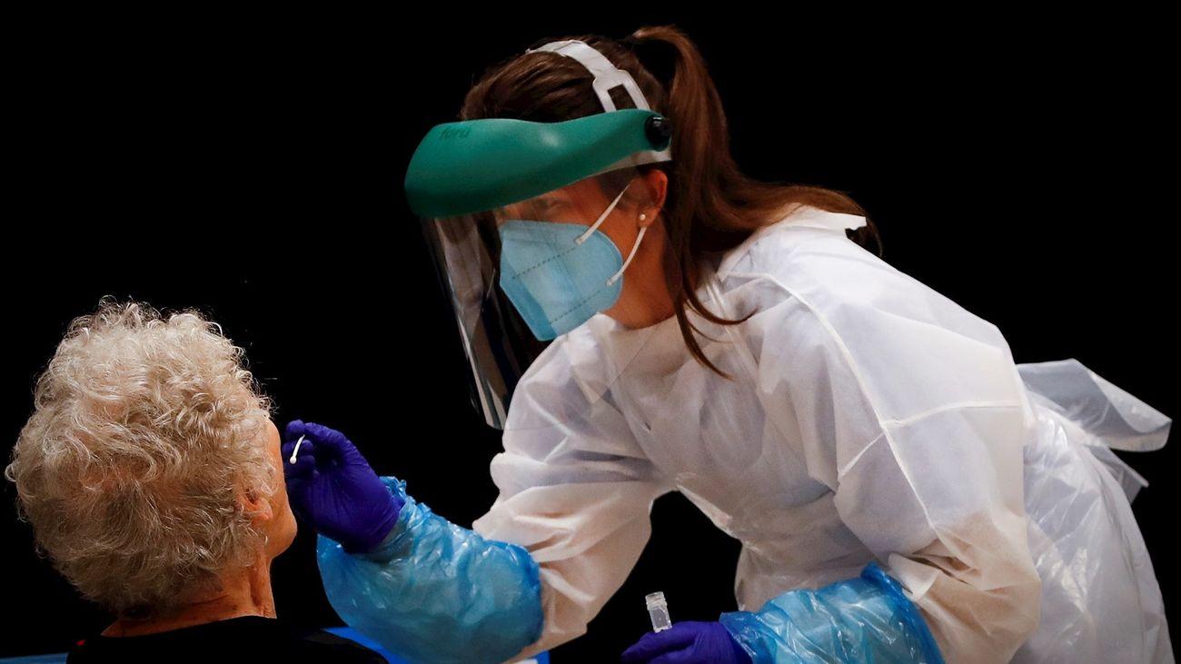 Una enfermera realiza una prueba PCR a una anciana