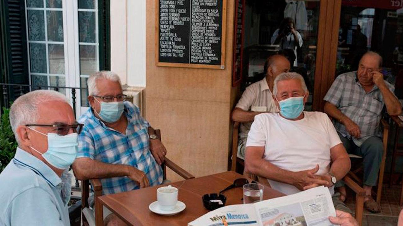 Un grupo de personas con mascarillas toma el café en la terraza de un bar