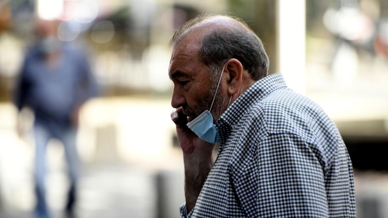 Un hombre hablando por teléfono en una calle de Madrid y con la mascarilla mal puesta el pasado 30 de julio