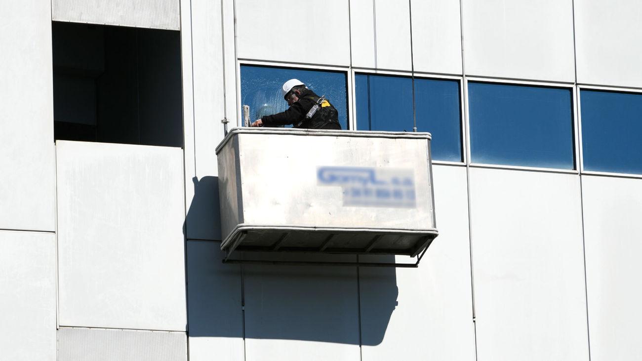 Un trabajador limpia los cristales de un edificio en Madrid