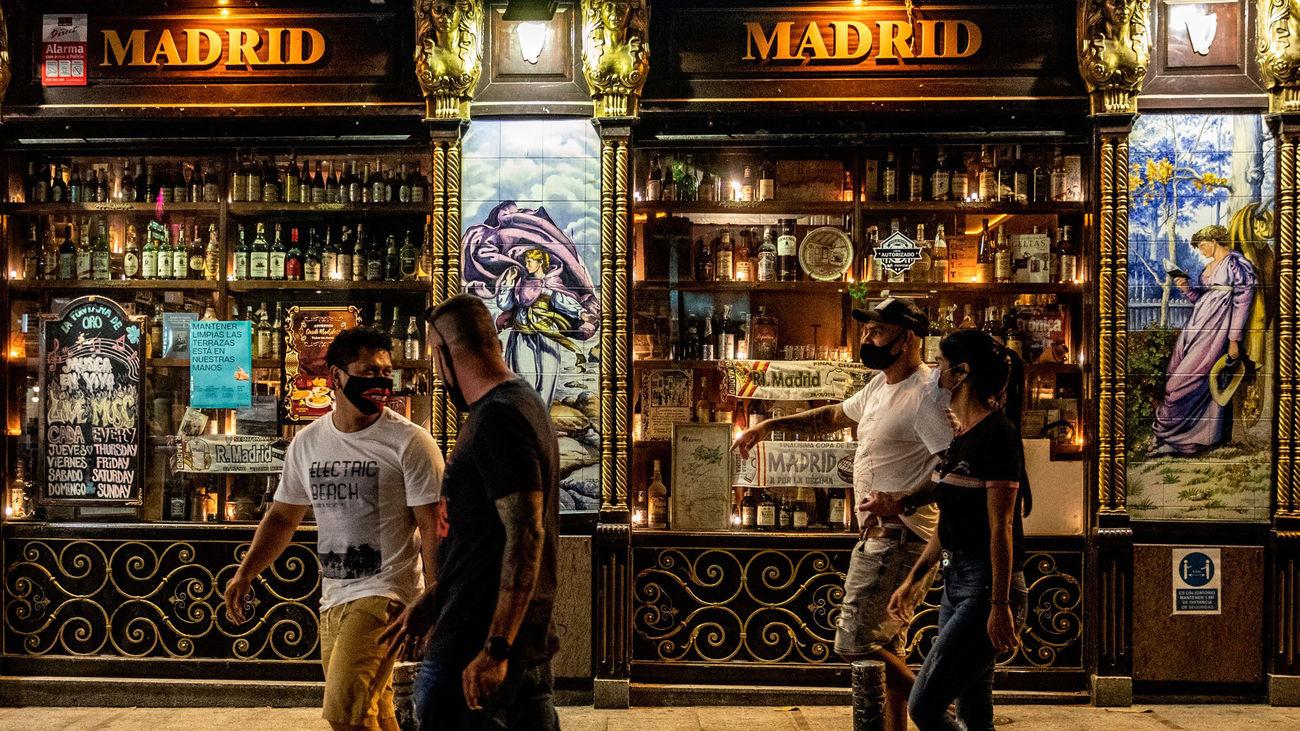 Un grupo de personas pasan frente a uno de los bares de la zona de Huertas y Plaza de Santa Ana en Madrid