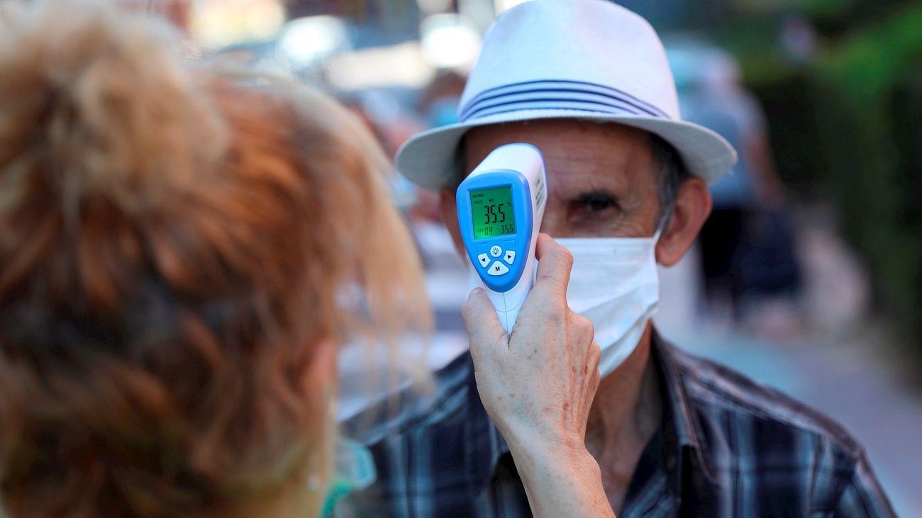 Una voluntaria toma la temperatura a un anciano