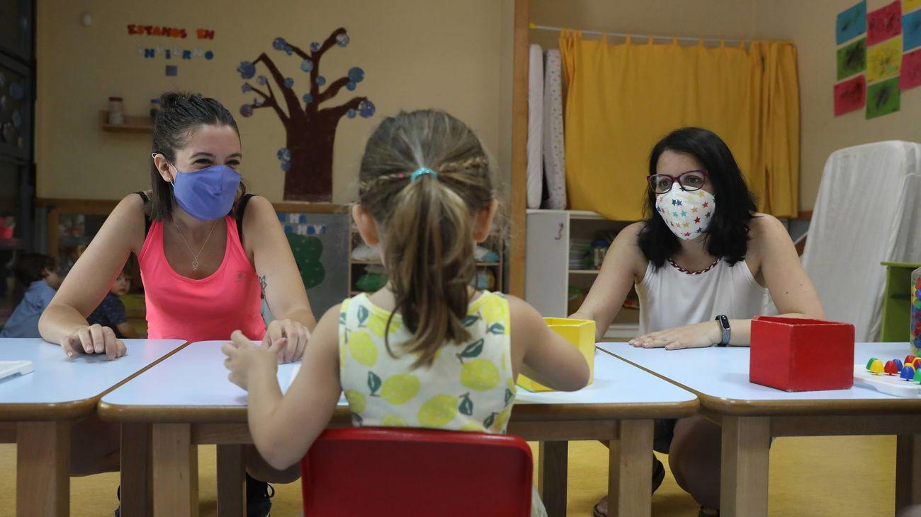 Dos profesoras atienden a una alumna de infantil en una escuela de Madrid