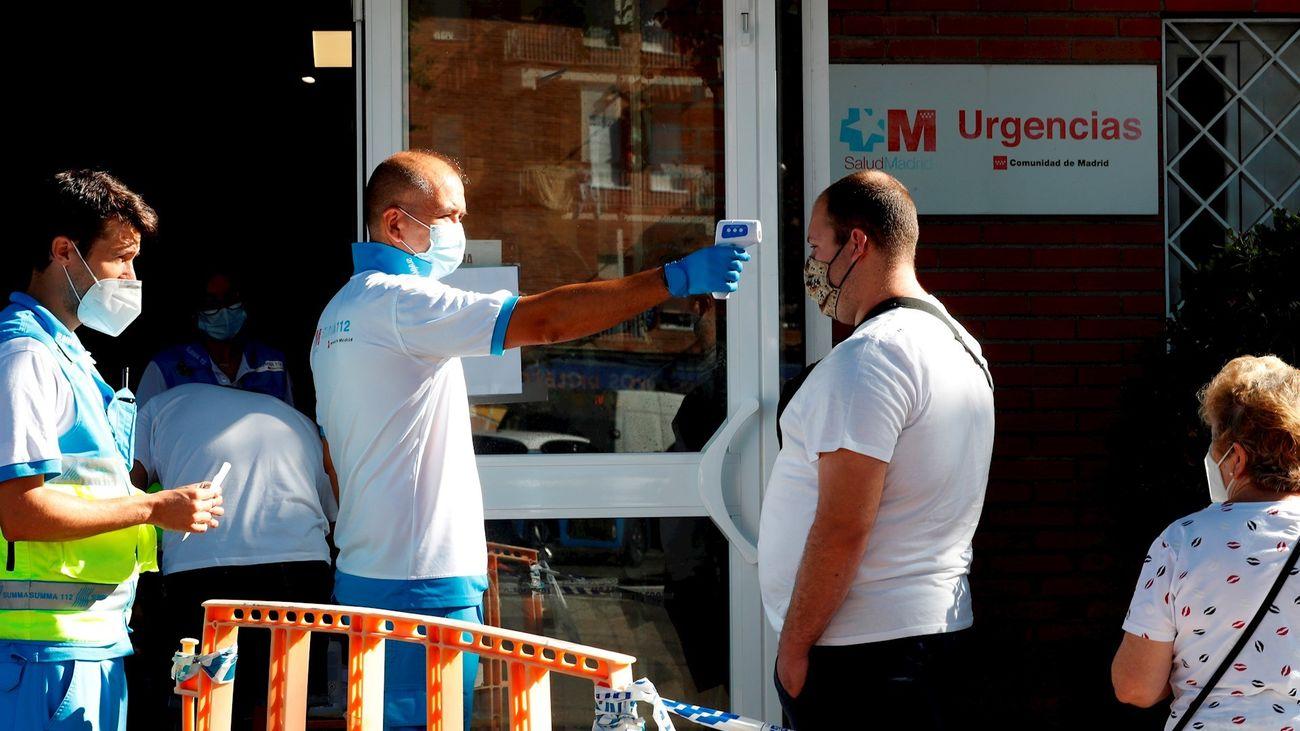 Un paramédico toma la temperatura a un ciudadano antes de acceder al centro de salud Reyes Católicos, de la localidad madrileña San Sebastián de los Reyes.