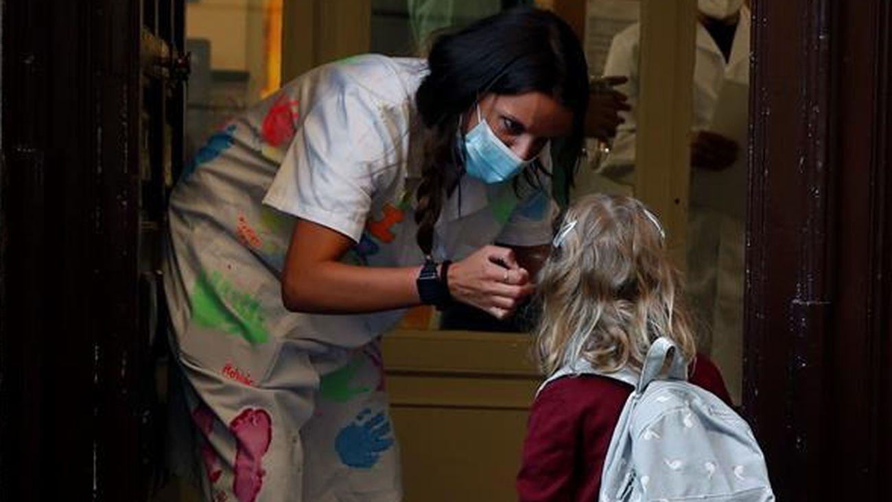 Una profesora habla con una alumna de Infantil en el primer día de la vuelta al cole en Madrid