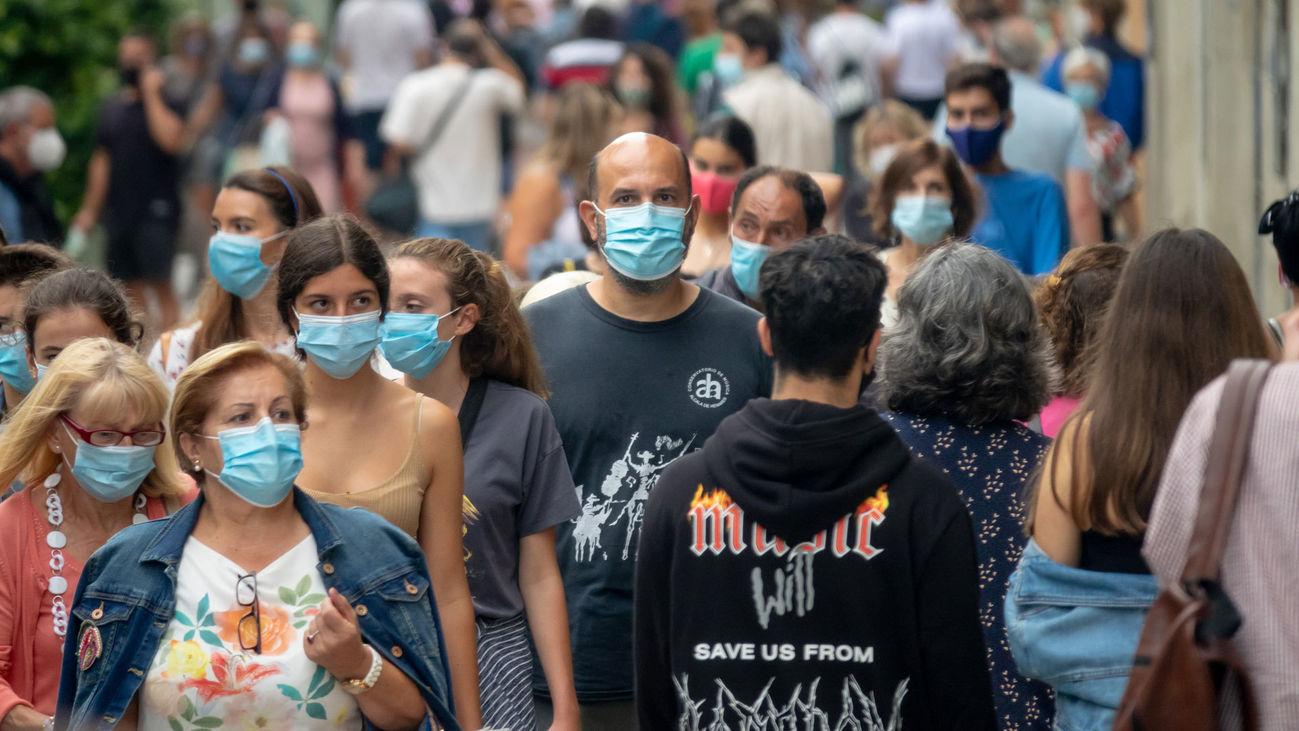Un grupo de personas pasean por la calle protegidos con mascarillas