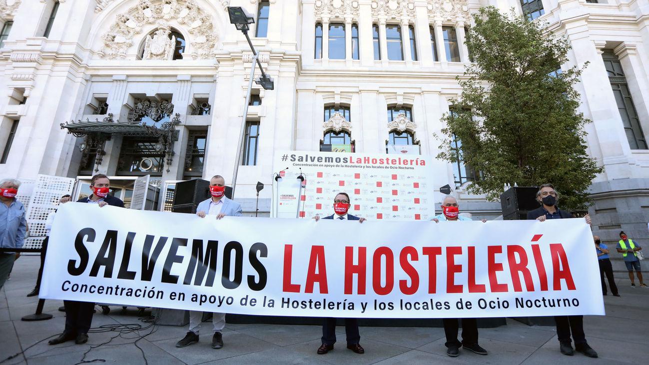Representantes de Hostelería de Madrid, la Plataforma por el Ocio, España de Noche y Hostelería de España sostienen una pancarta que pide salvar la hostelería ante el Palacio de Cibeles