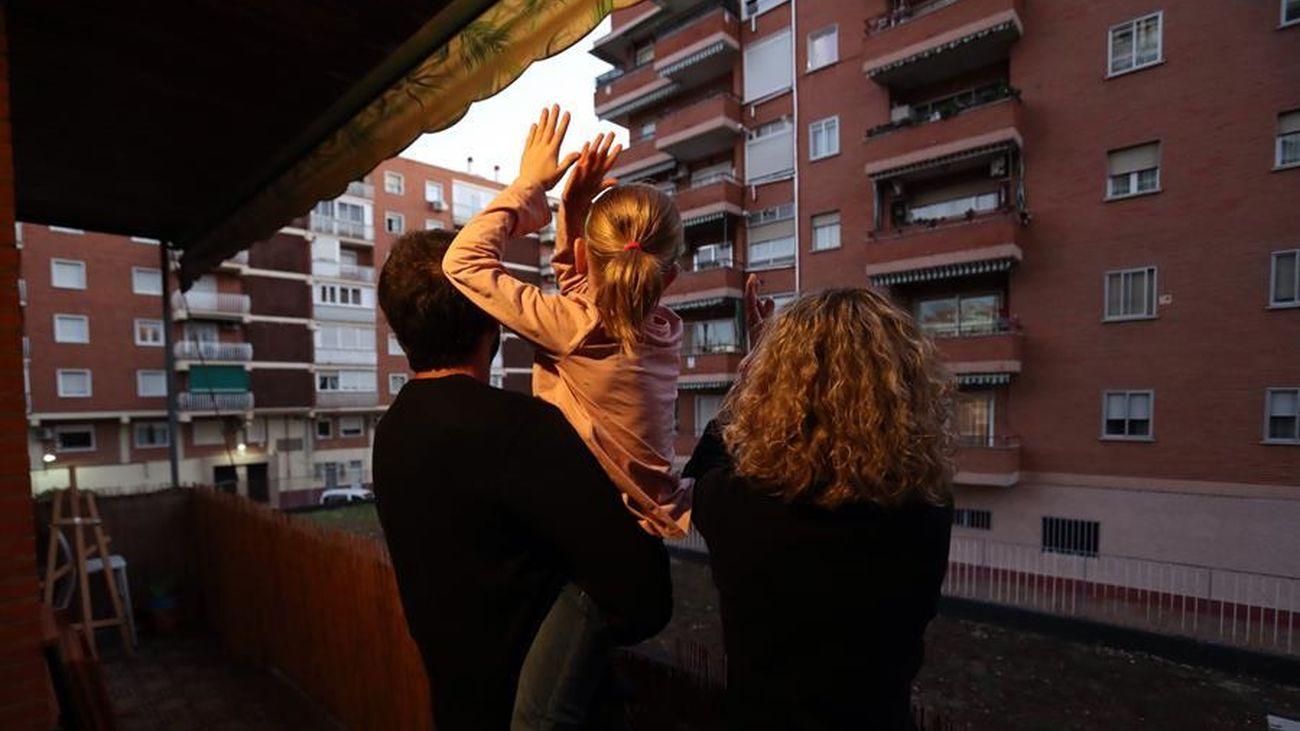 Una familia madrileña se asoma al balcón