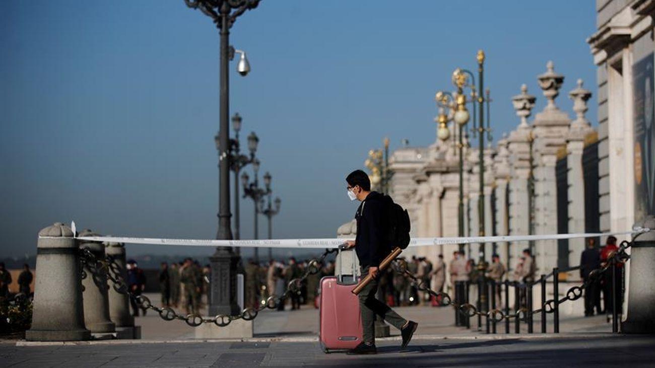 Un persona con una maleta al lado del Palacio Real