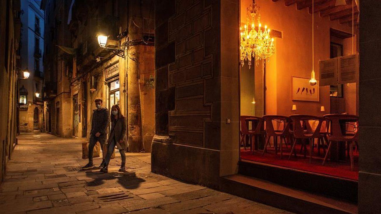Dos personas pasean en la noche de Barcelona