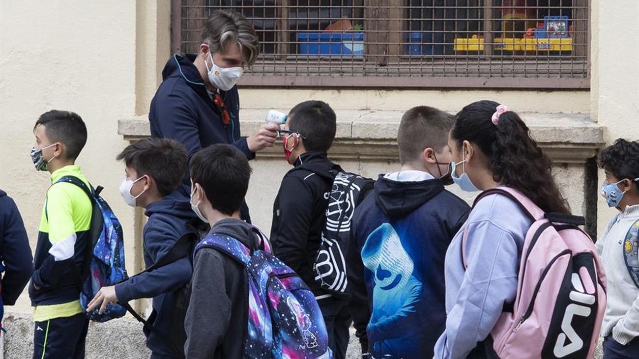 Un profesor toma la temperatura a la entrada del colegio