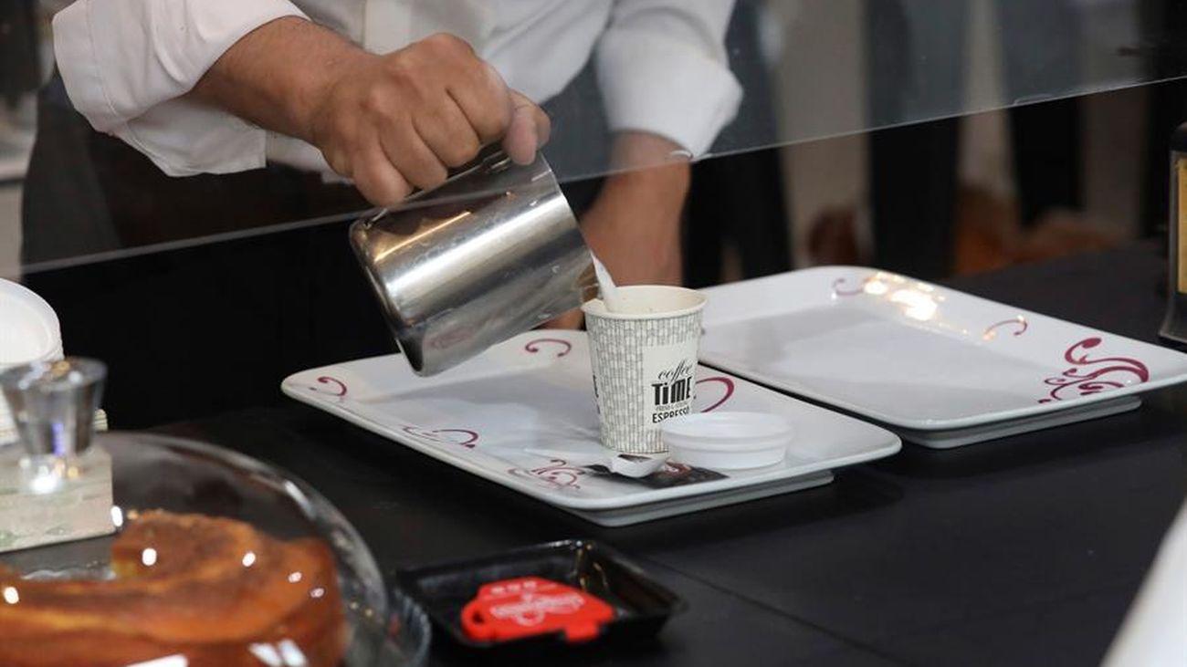 Un camarero sirve un café en un bar
