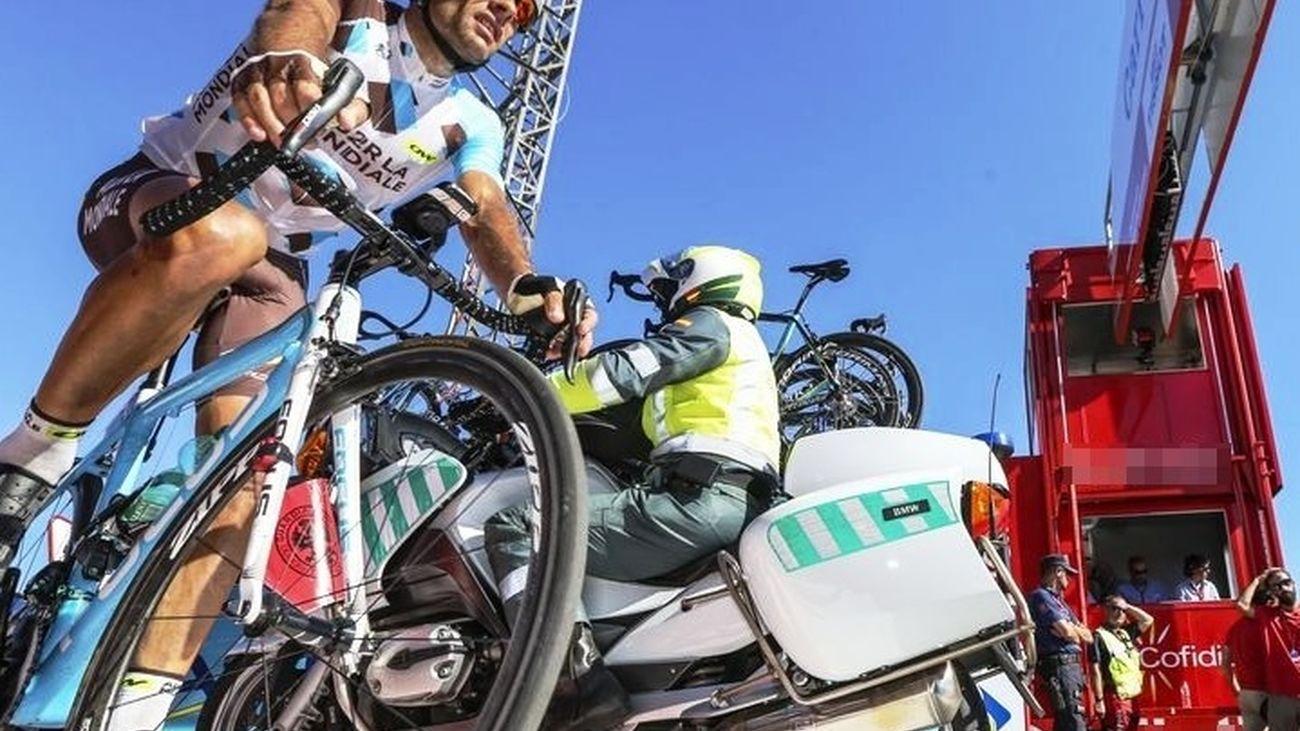 Un ciclista y un agente de se cruzan bajo la línea de meta