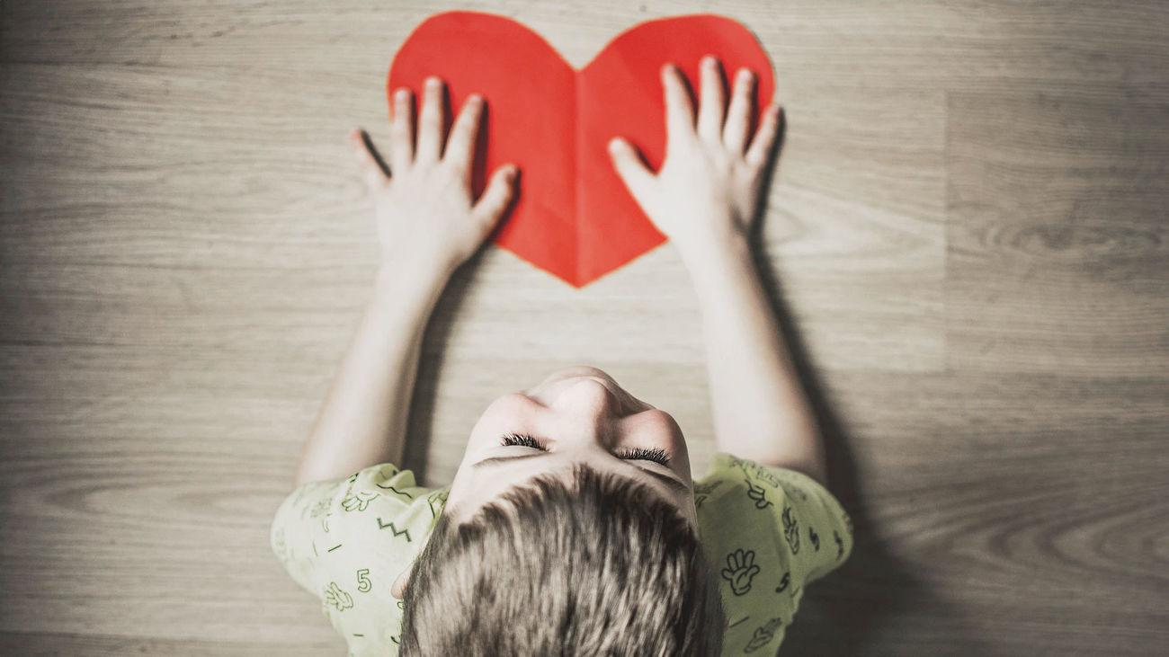 Un niño sostiene un corazón rojo