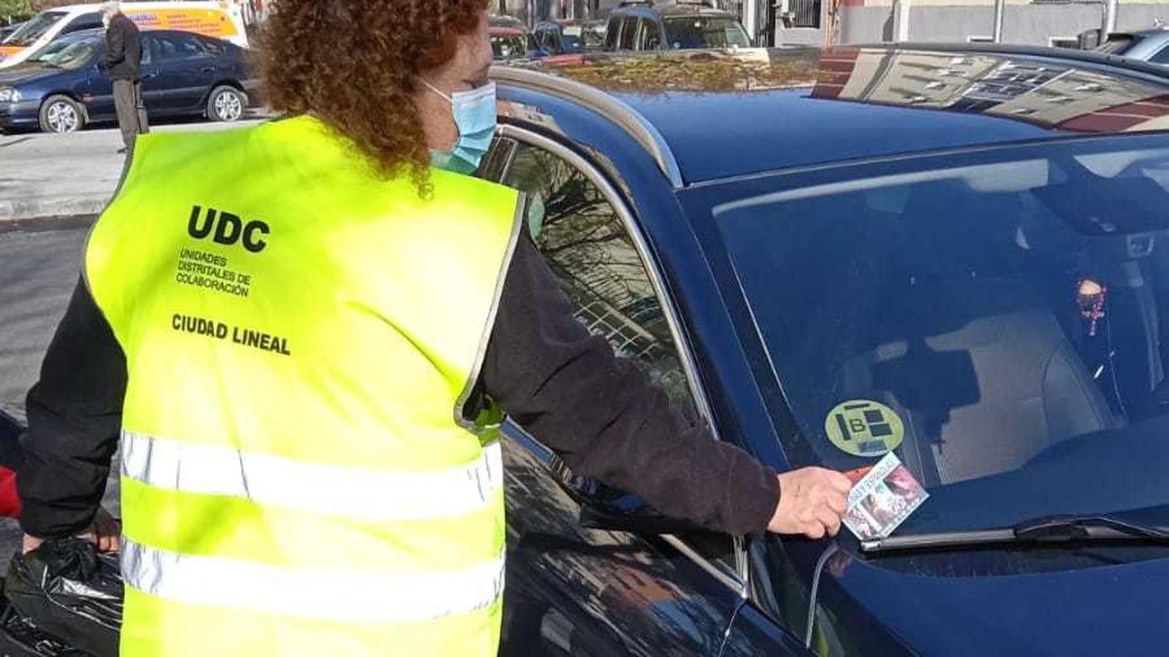 Una mujer quita publicidad de prostitución en un coche de Ciudad Lineal