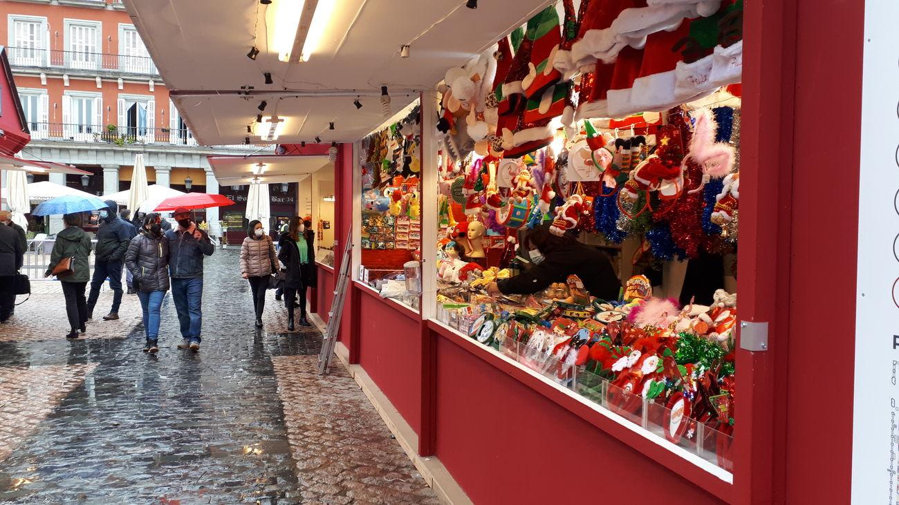 Paseantes y compradores frente a los puestos navideños de la Plaza Mayor