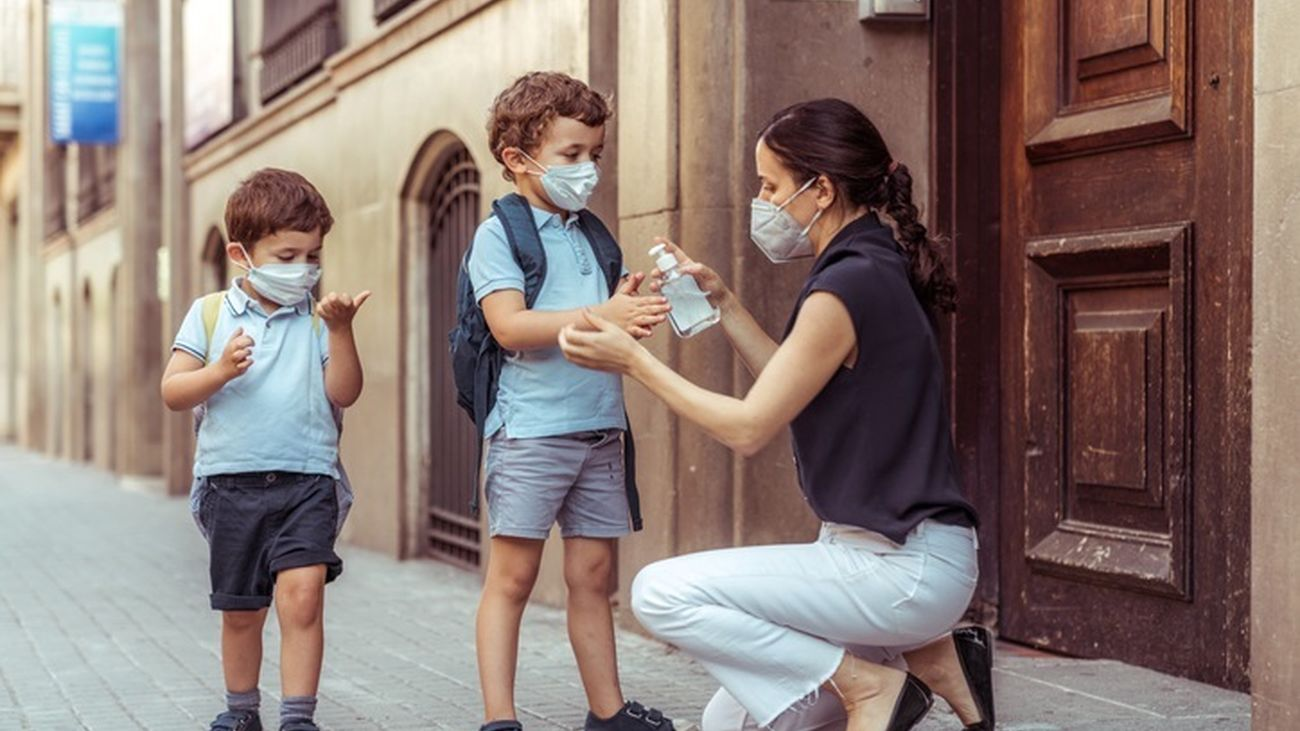 Madre echando a sus hijos gel hidroalcohólico