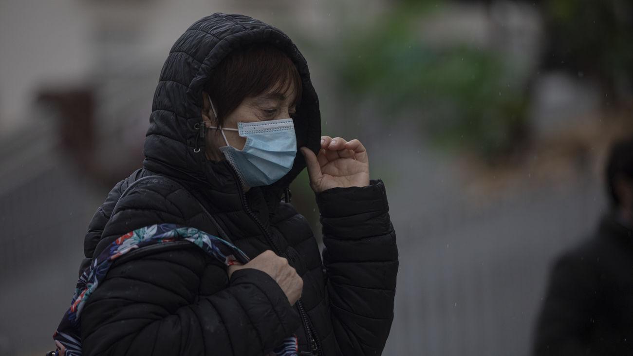 Una mujer camina con frío por Madrid