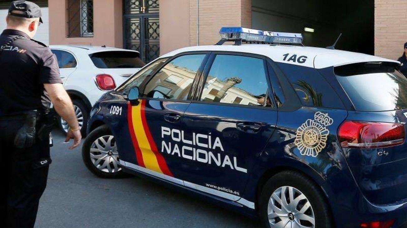 Agente de Policía Nacional junto a un coche patrulla