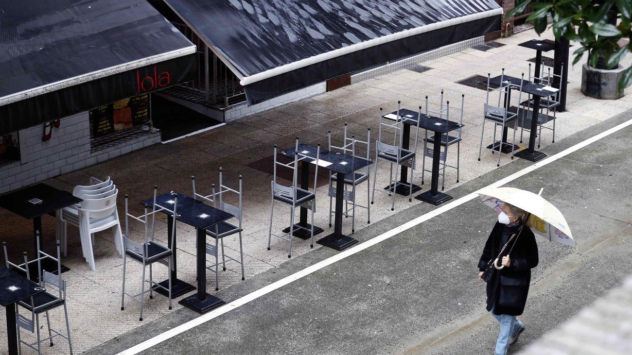 Una mujer pasea ante una terraza vacía