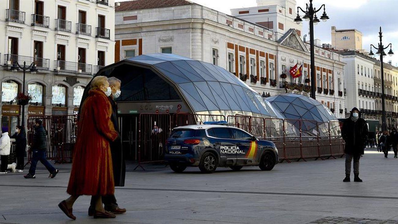 Una pareja pasea con mascarilla por la Puerta del Sol