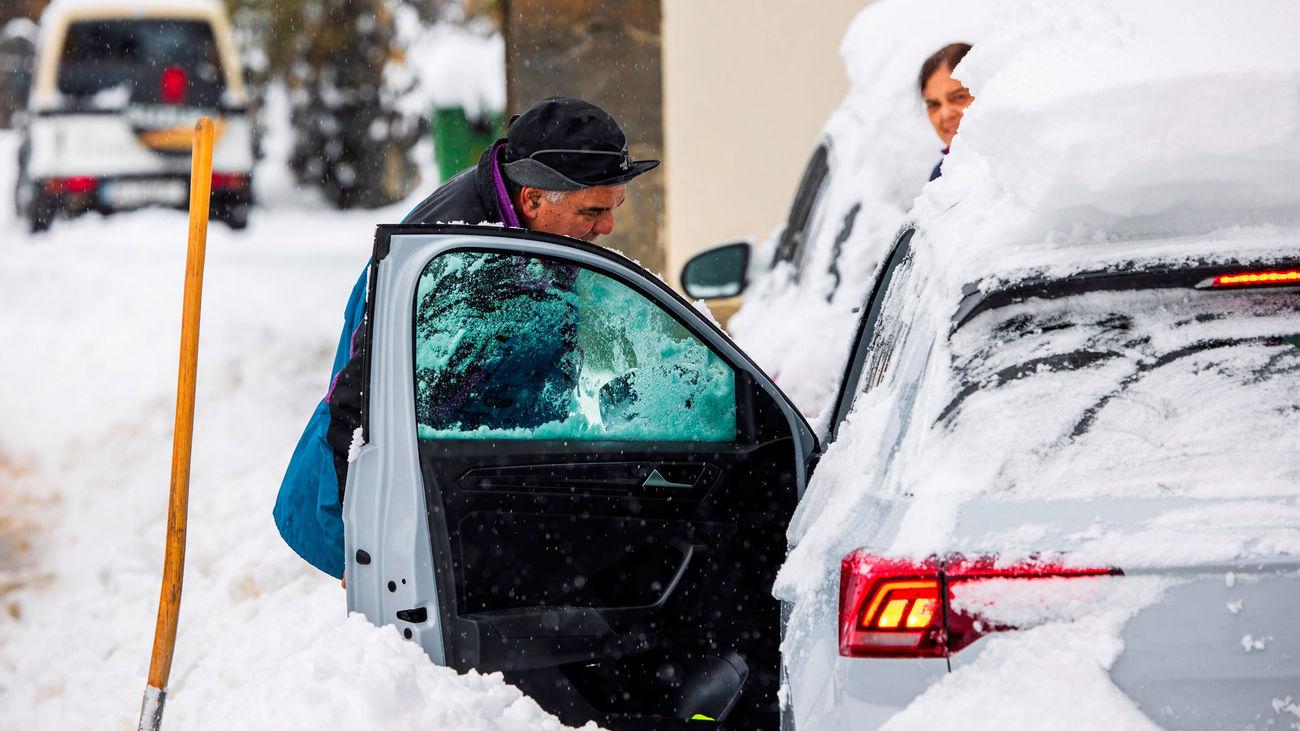 Una persona quita la nieve acumulada para entrar a su coche