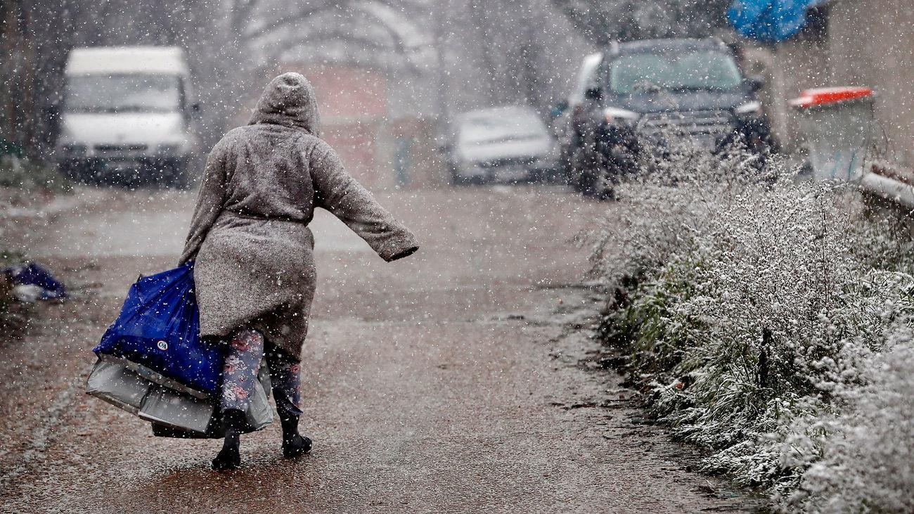 Una vecina de la Cañada Real camina bajo la nieve