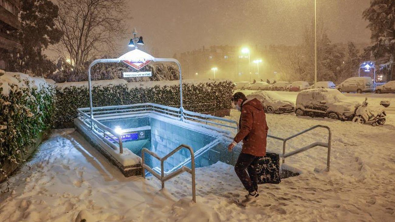 Entrada a una estación de Metro de Madrid cubierta por la nieve