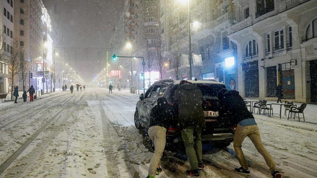 Jóvenes empujan un coche en plena Gran Vía bajo la nieve