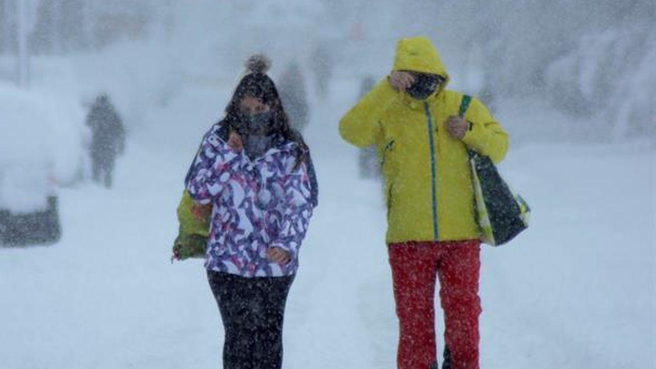 Dos personas caminan por la calle en plena nevada en Madrid