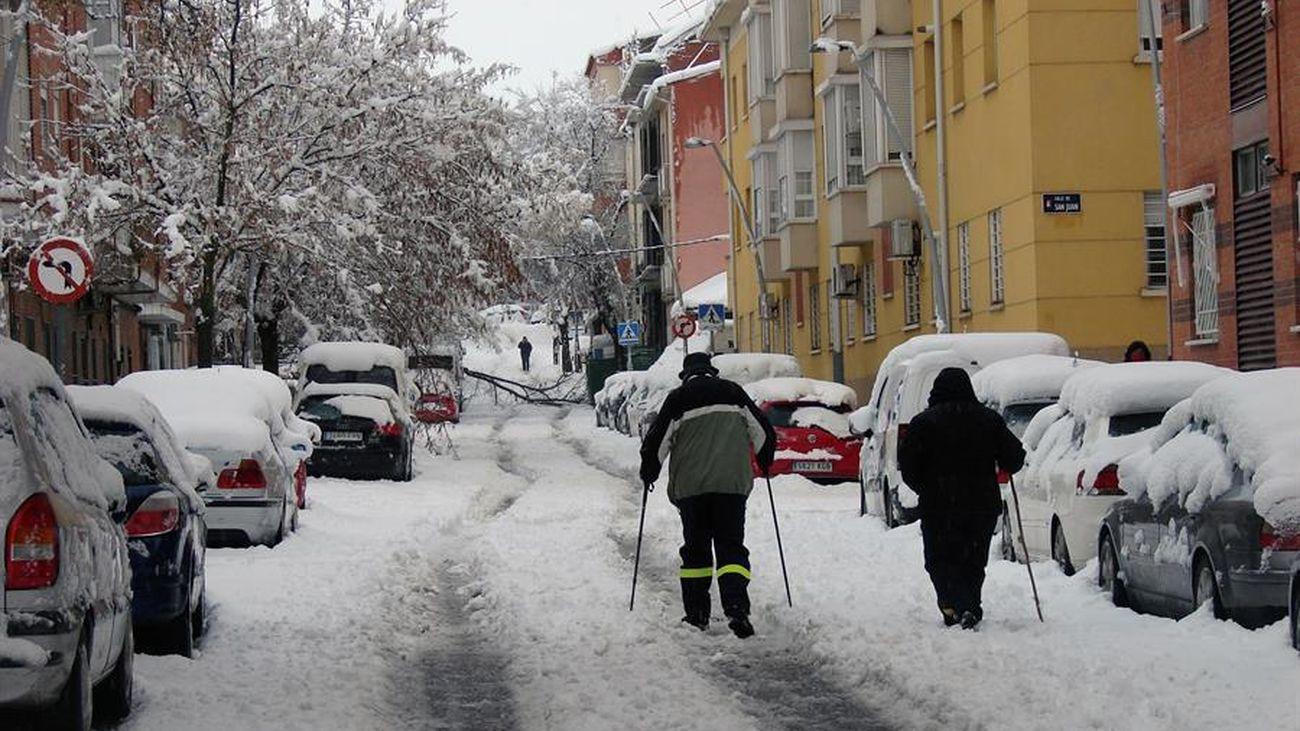 Dos personas caminan entre la nieve en una calle de Madrid