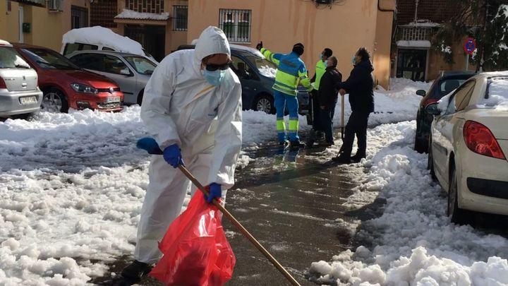 Una médico del 112 barre la nieve de una calle de Majadahonda para poder trasladar a un paciente con Covid