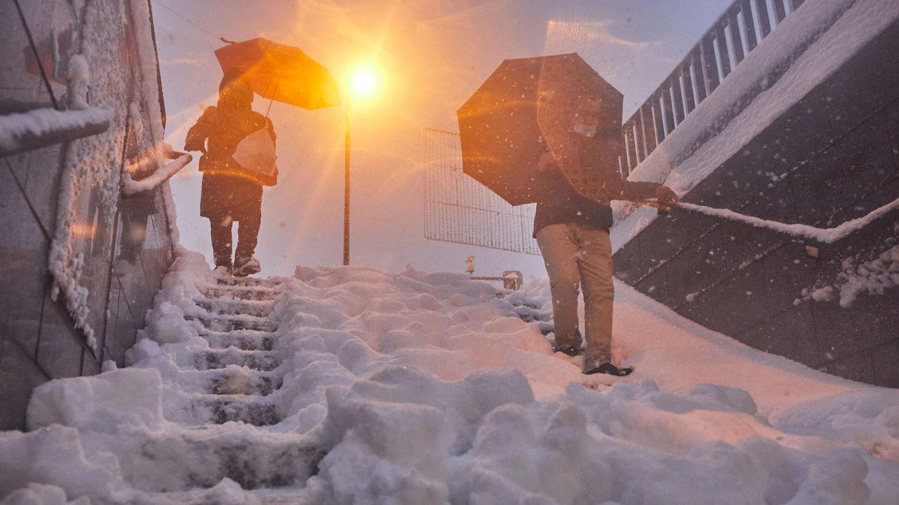 Dos personas bajan las escaleras de una entrada de Metro durante la gran nevada de la borrasca Filomena