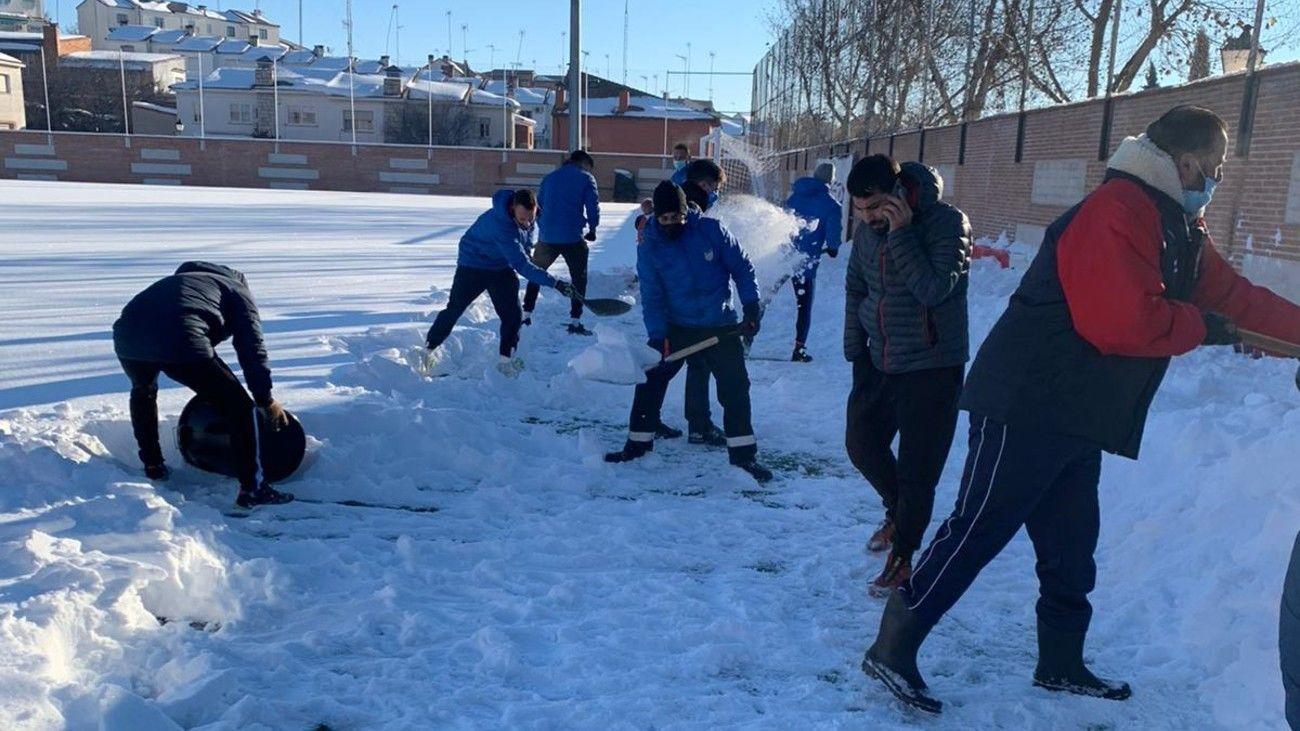 Voluntarios quitan la nieve del estadio del Navalcarnero