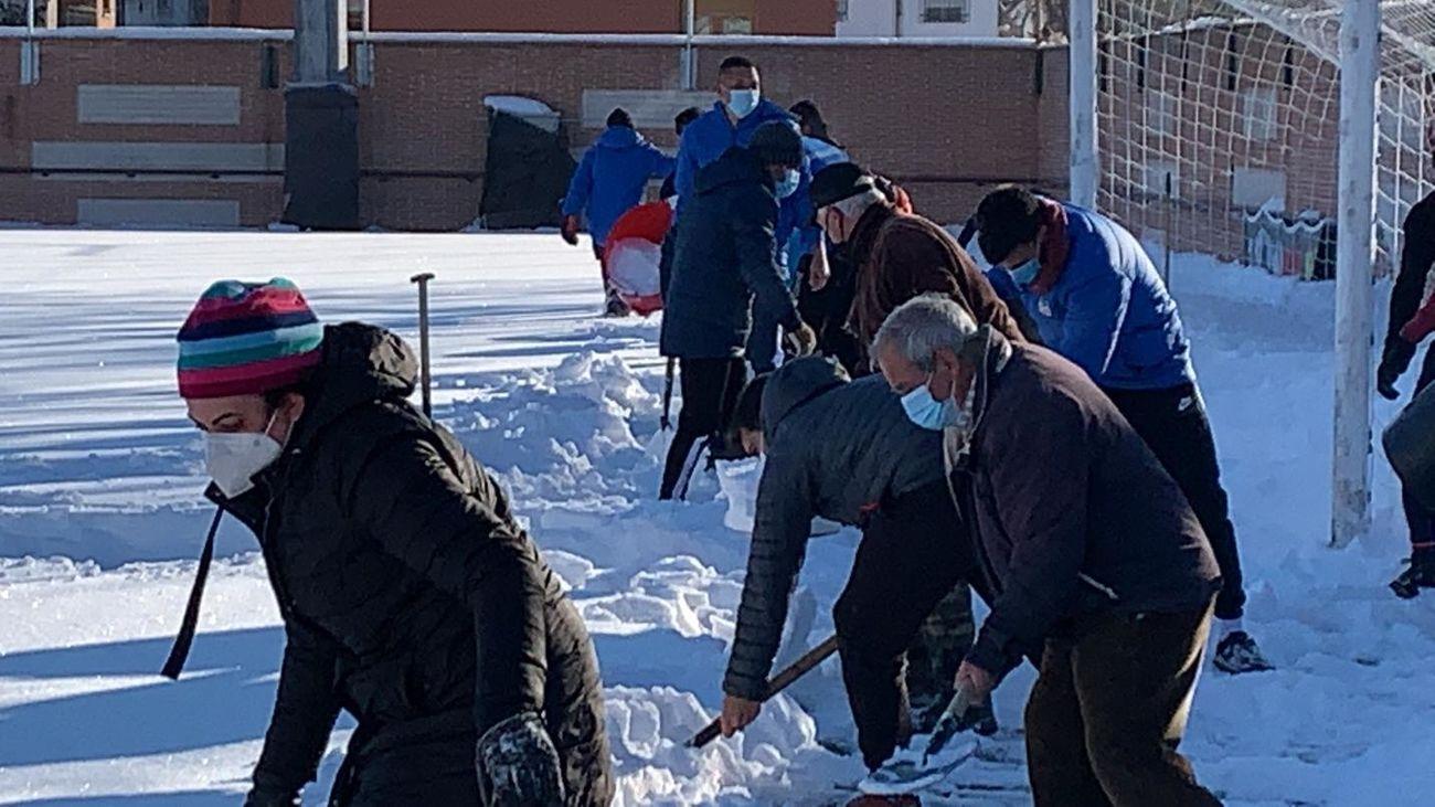 Gente del Navalcarnero limpian la nieve de su estadio