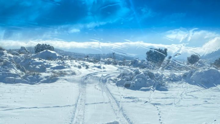 Un vecino de El Molar retira con una excavadora la nieve que mantiene incomunicadas varias fincas