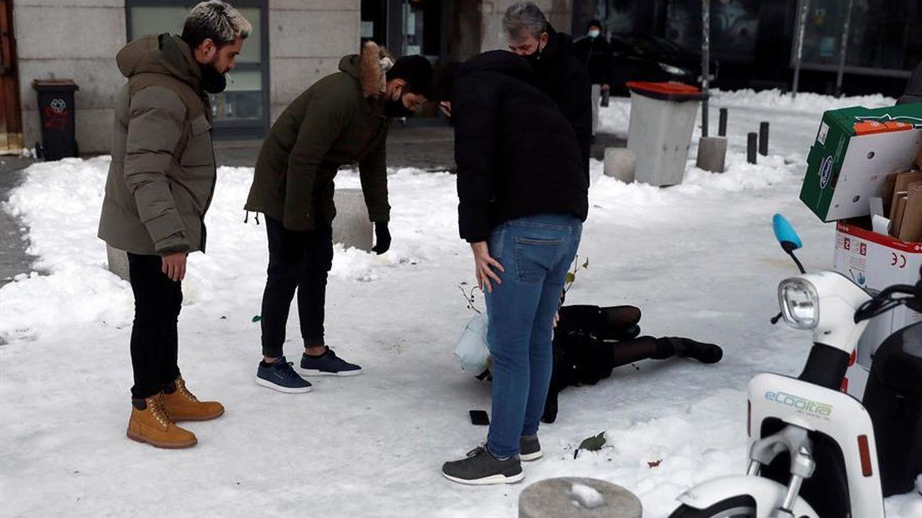Madrileños atienden a una persona en el suelo tras caer por el hielo