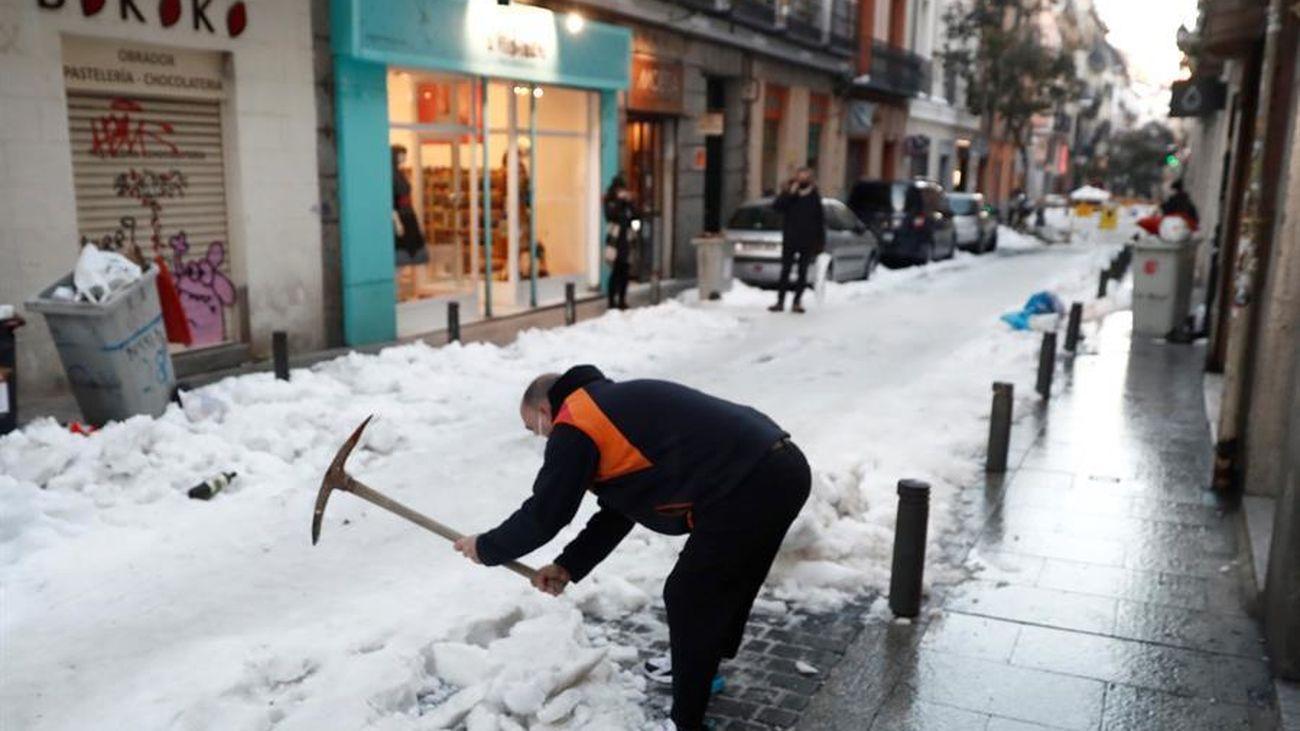 Operarios quitan la nieve y el hielo de una calle de Madrid