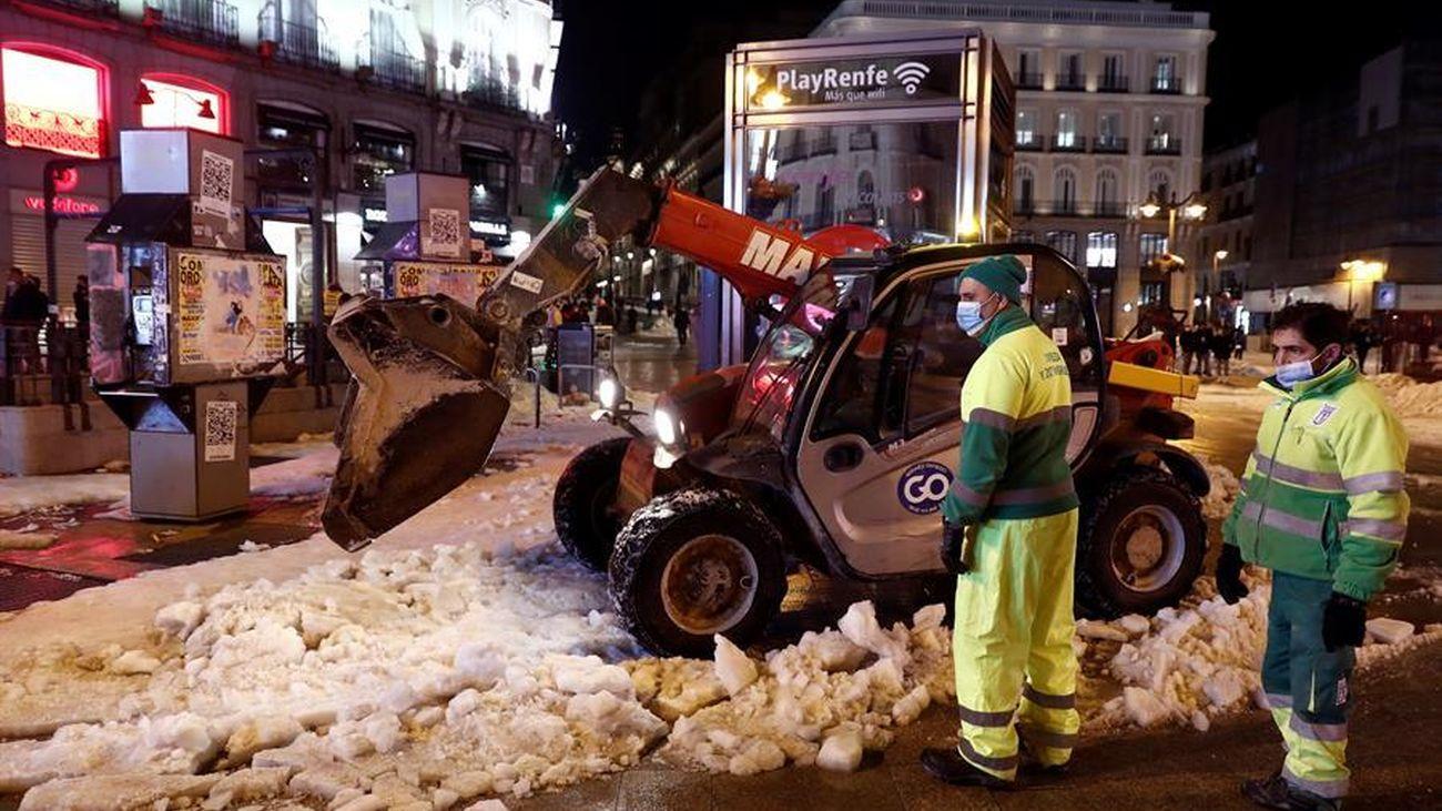 Operarios retirando la nieve en el centro de Madrid