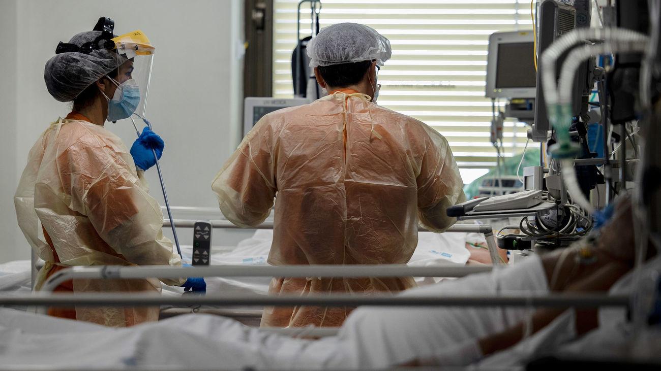 Dos sanitarios atienden a un paciente en la UCI de enfermos de coronavirus en el hospital  Ramón y Cajal