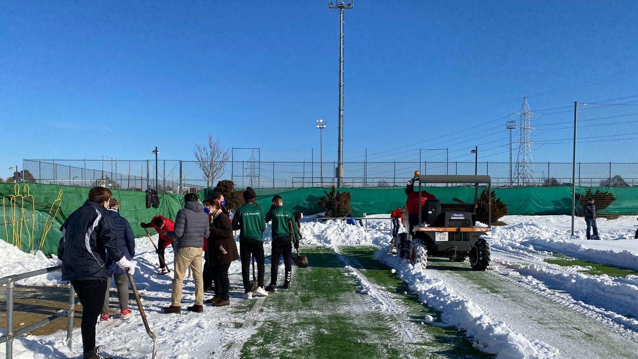 Los miembros de los clubes deportivos de Pozuelo retirando la nieve