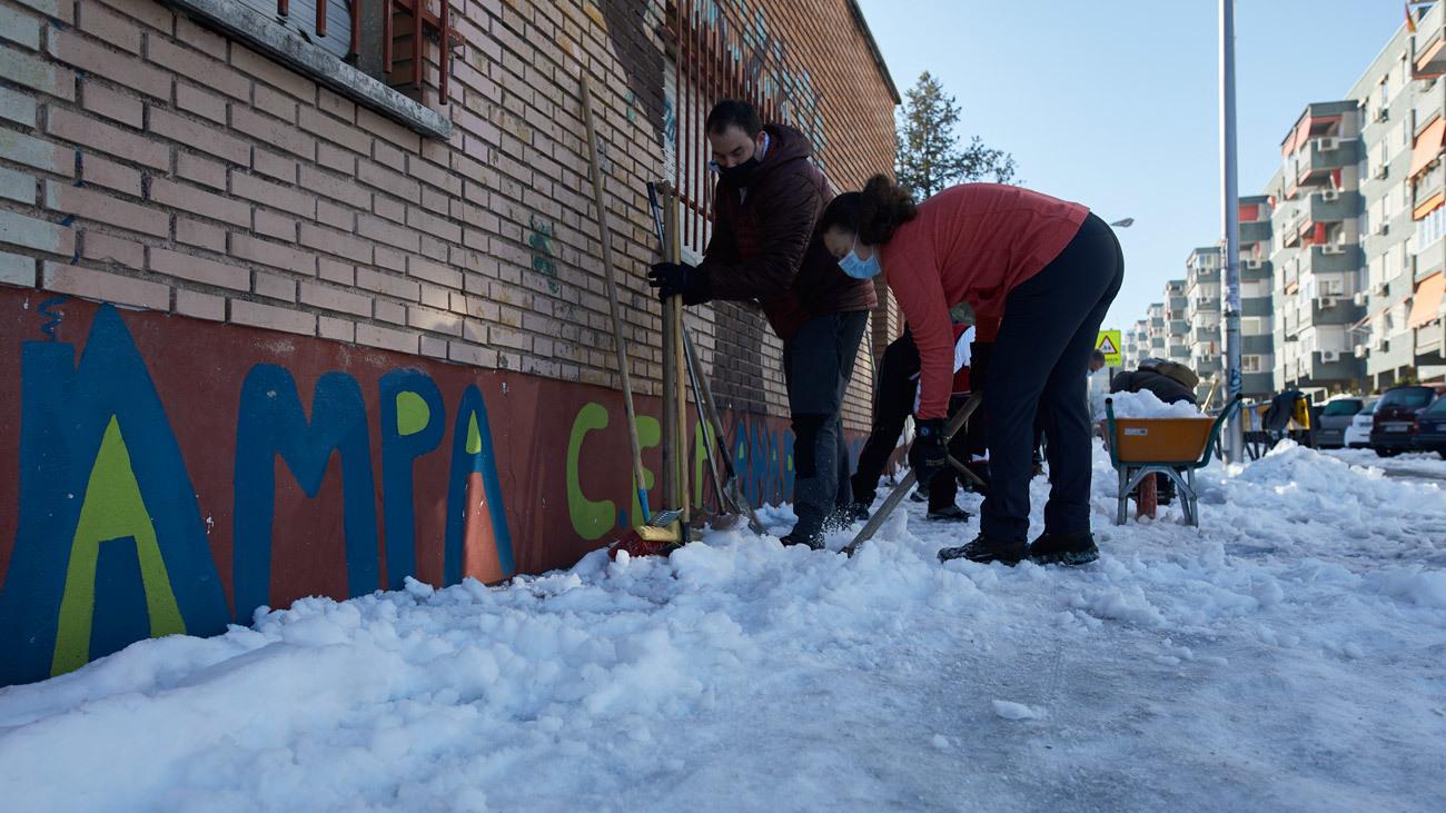 Padres de alumos ayudan a retirar nieve de los exteriores de un colegio de Madrid